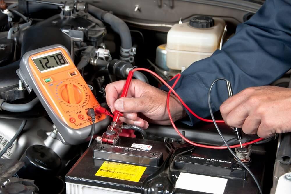 Service mechanic testing a car battery