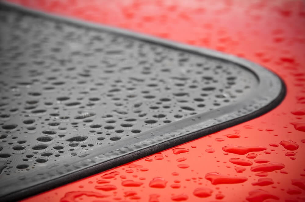 Close up of window rubber seal on red car.
